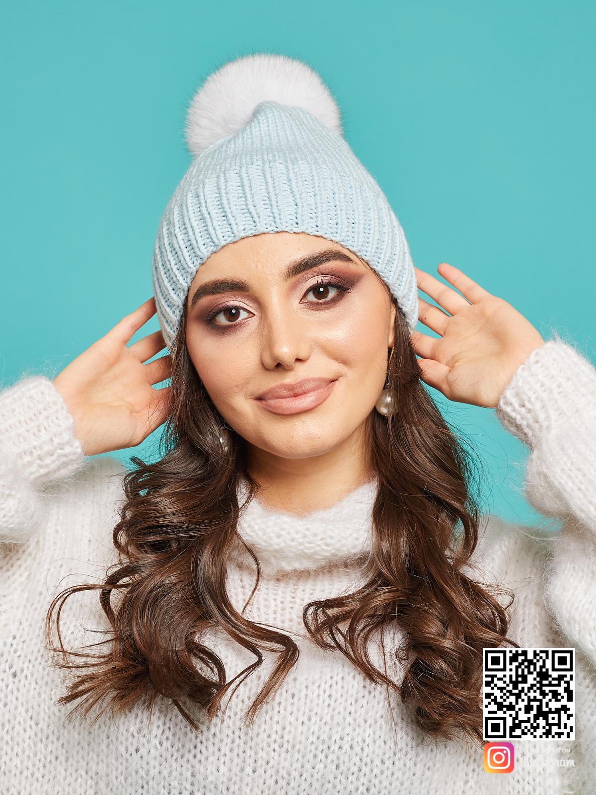 На фотографии голубая шапка с помпоном от Shapar, бренда вязаной одежды и головных уборов ручной работы в интернет-магазине связанных спицами вещей.