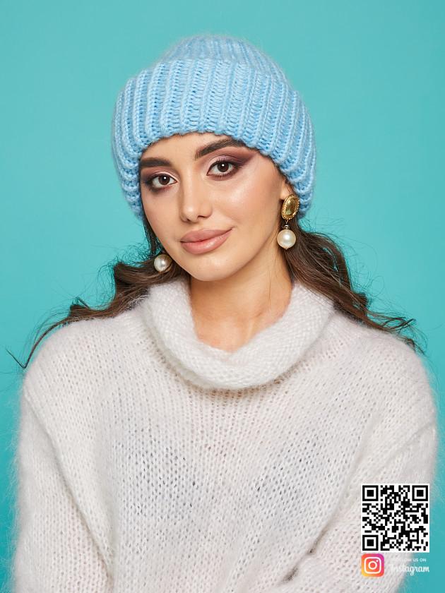 На фотографии голубая вязаная шапка от Shapar, бренда одежды и головных уборов ручной работы в интернет-магазине связанных спицами вещей.