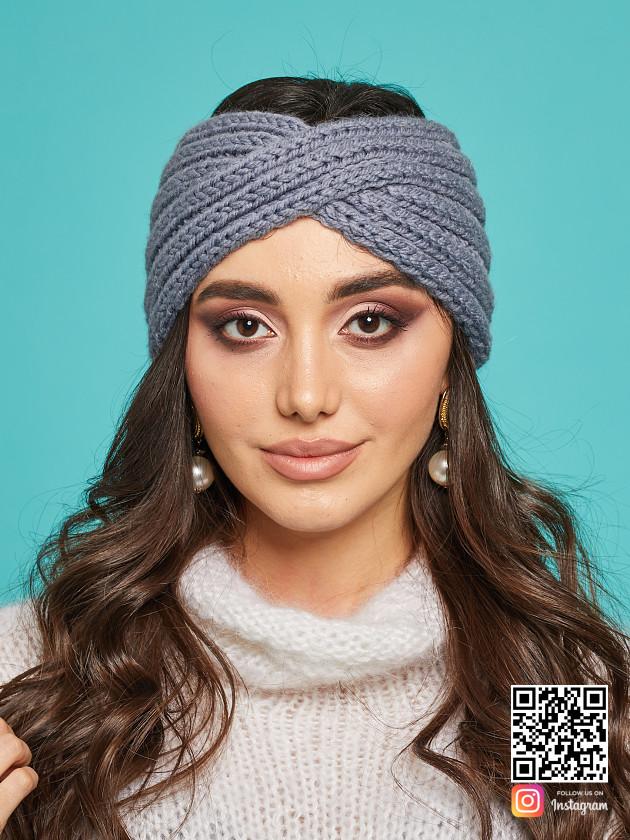 На фотографии серая повязка на голову от Shapar, бренда вязаной одежды и головных уборов ручной работы в интернет-магазине связанных спицами вещей.