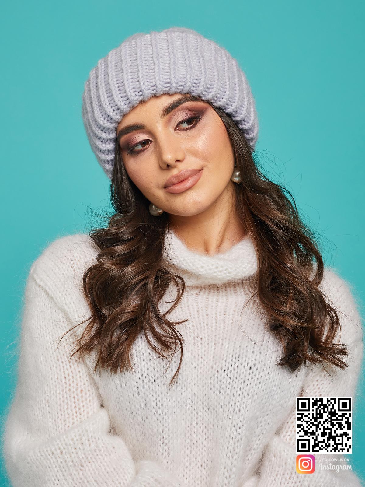 На фотографии серая вязаная шапка от Shapar, бренда одежды и головных уборов ручной работы в интернет-магазине связанных спицами вещей.