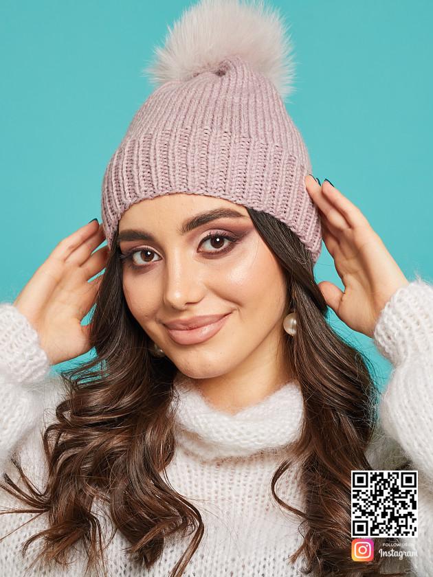 На фотографии шапка с помпоном из натурального меха от Shapar, бренда вязаной одежды и головных уборов ручной работы в интернет-магазине связанных спицами вещей.