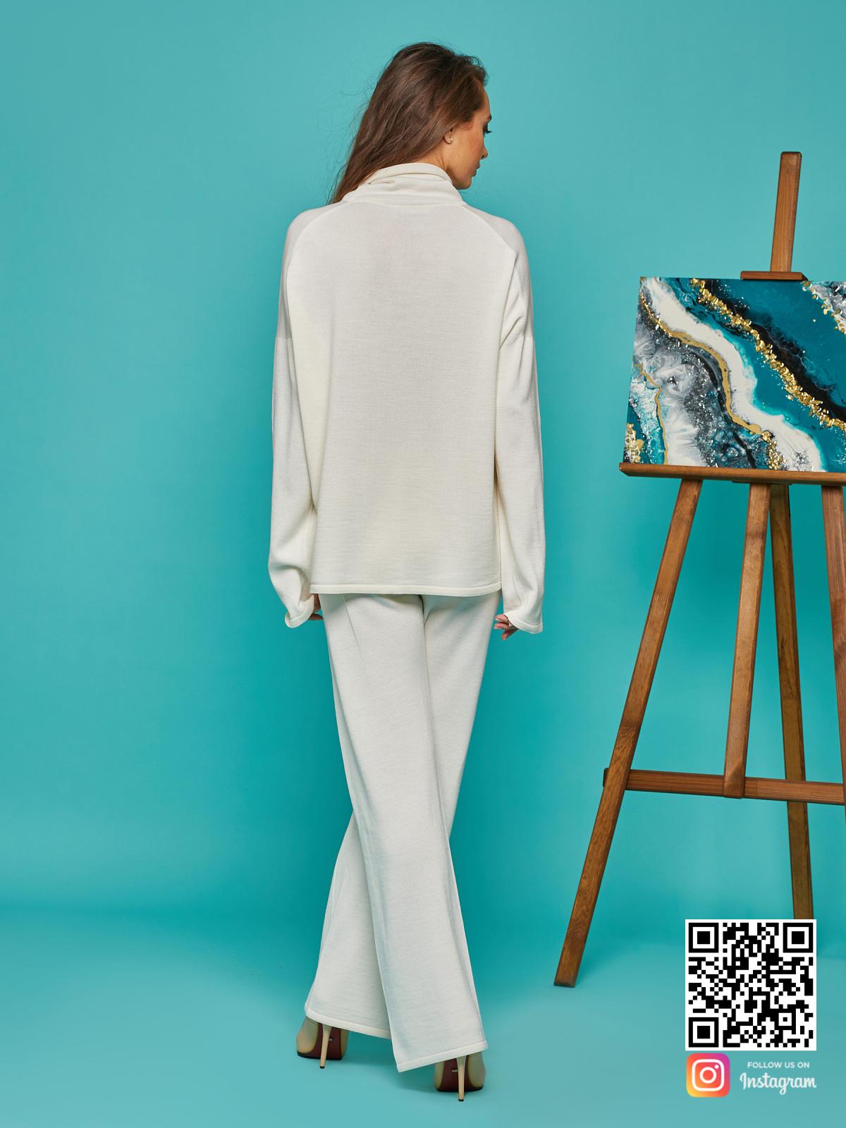 На второй фотографии женский белый костюм оверсай со спины от Shapar, бренда вязаной одежды ручной работы в интернет-магазине связанных спицами вещей.