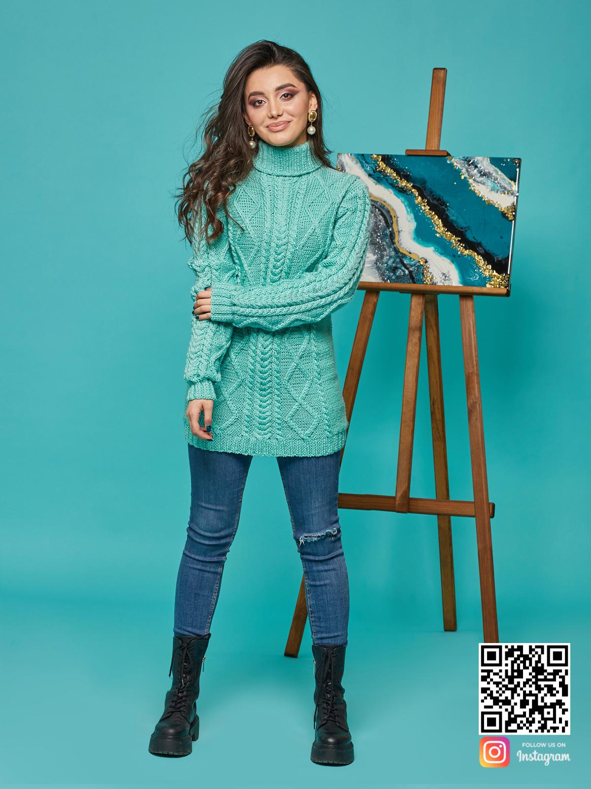 На фотографии длинный вязаный свитер от Shapar, бренда женской одежды ручной работы в интернет-магазине связанных спицами вещей.