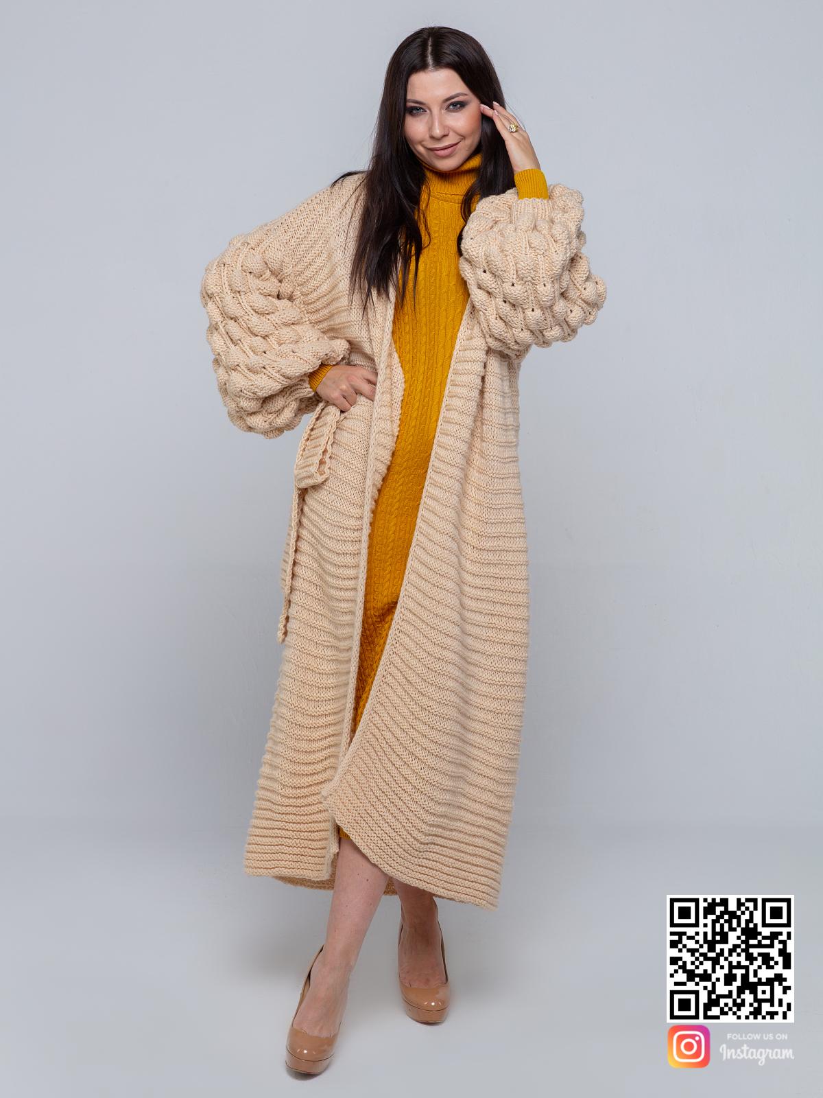 На фотографии длинный бежевый кардиган от Shapar, бренда вязаной одежды ручной работы в интернет-магазине связанных спицами вещей.